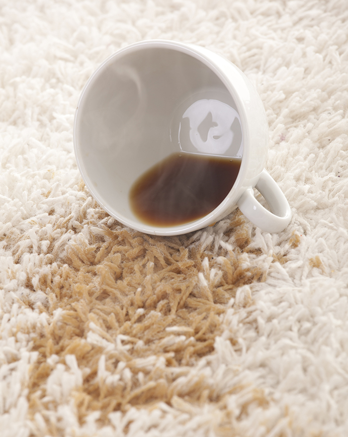 18839181 - a glass of spilled coffee on brand new carpet is sure to leave a stain.